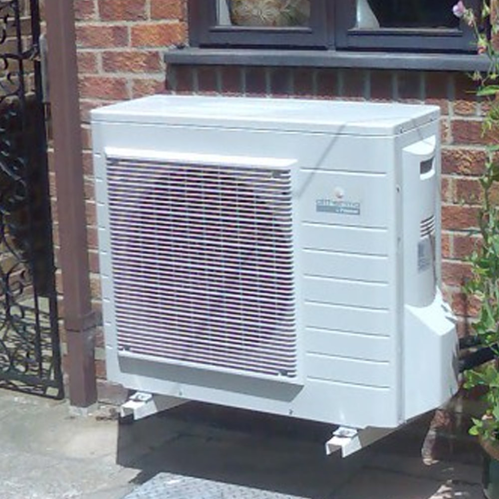Image of an air source heat pump attached to the wall of a house.