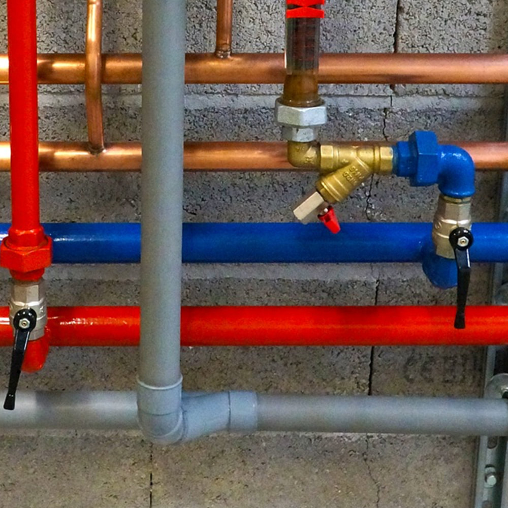 Arco plumbers in Romford. A close up picture of horizontal pipes. Top two are copper, then blue, red and grey.