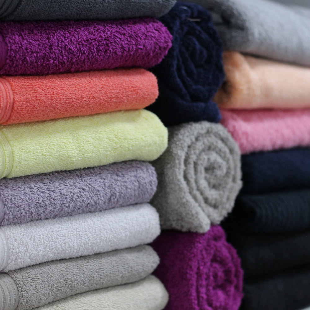 A tower of different coloured towels that are folded up.