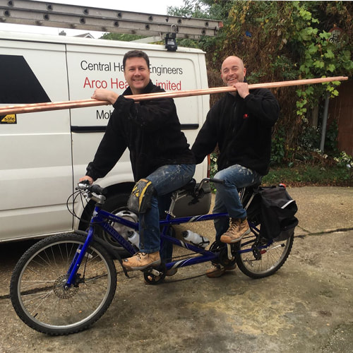 Photo of Martin and Craig on a tandem bike carrying pipes. Arco enjoy what they do and have a fun and friendly disposition